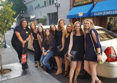 girls posing next to limousine