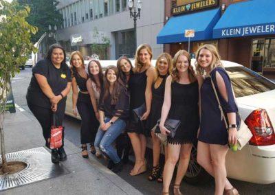 girls posing next to limousine